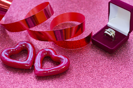 Valentines concept with a golden ring in a red box glitter red background, close up