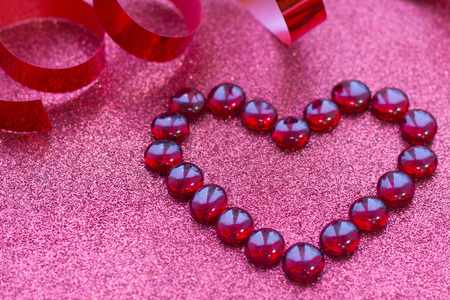 Concept of Valentines Day with red heart glitter red background, close up
