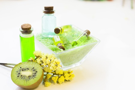 Fruit aromatherapy concept with essential oil in bottles, bath sea salt, kiwi and flower, white background, close up 스톡 콘텐츠