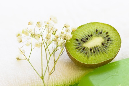 Spa, Aromatherapy, Natural Cosmetic concept with a bar of soap and fresh kiwi on towels, white background, close up