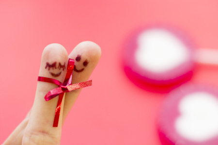 St. Valentines Day concept with finger art happy couple hugging and hearts, red background, close up