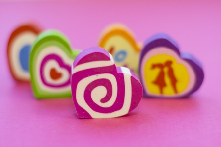 St. Valentines Day or Anniversary concept with decorative colorful eraser hearts, pink background,close up Stock Photo