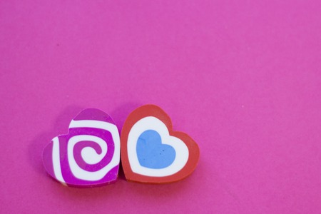 St. Valentines Day or Anniversary concept pink background with decorative colorful heart erasers, close up, tio view