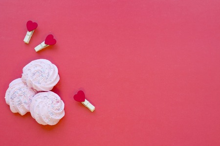 The concept of St.Valentines Day with marshmellows, red background top view