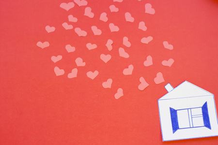 The concept of St.Valentines Day with paper house and paper hearts, red background top view Stock Photo
