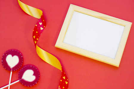 The concept of St.Valentines Day with a blank wooden photo frame, red background top view, copy space Stock Photo