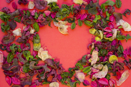The concept of St.Valentines Day, red background with a frame of rose petals and leaves, top view, copy space