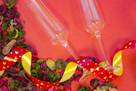 The concept of St.Valentines Day with two champagne glasses, red background with a corner of rose petals and leaves top view, copy space Stock Photo