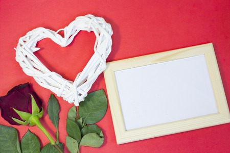 The concept of St.Valentines Day with a beautiful red rose and wooden photo frame, red background, top view