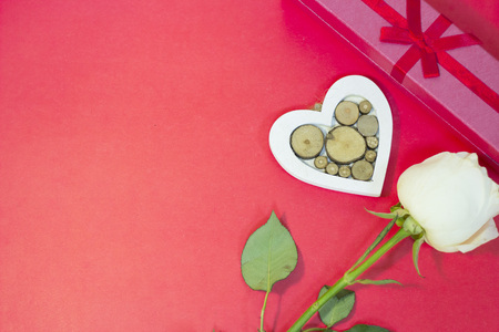 The concept of St.Valentines Day with a beautiful white rose, a gift box and a wooden heart, top view, copy space