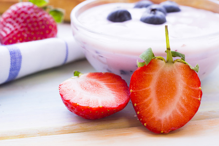Romantic French or Rural Breakfast with homemade youghurt and fresh blueberries and strawberry. Napkin and wood as a background, close up