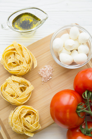 Preparing Food Concept. Ingredients for cooking pasta with mozzarella, olive oil and tomatos on a wooden cutting board, close up, top view Stock Photo