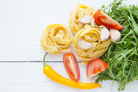 Preparing Food, Vegeterian, Vegan Concept. White wooden background with fetticcini, tomato slices, garlic, yellow cayenne pepper and rucola salad leaves, copy space, top view