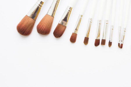 Make Up Beauty Concept. Set of make up brushes for lipstick, eyeshadows, foundation, powder, eyeliner and blusher on white background with copy space, top view, flat lay Stock Photo