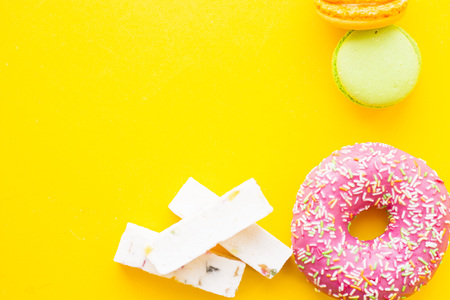 Delicious dessert: fresh donut in a pink glaze, vanilla fudge and fruit macaroons on a yellow background with copy space, top view