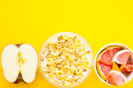 Delicious breakfast: fresh juicy apple cut in half, a bowl of muesli and a ceramic bowl with sliced grapefruit on a yellow background with copy space, top view