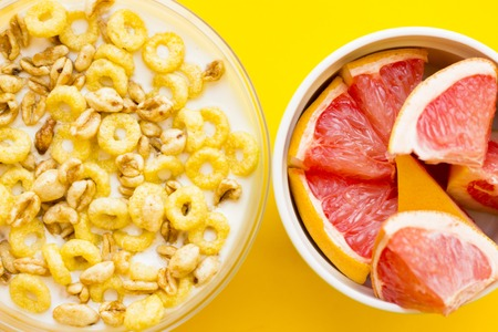 Delicious breakfast: a bowl of muesli and a ceramic bowl with sliced grapefruit on a yellow background with copy space, top view