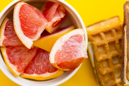Delicious breakfast: fresh waffles and a bowl of sliced grapefruit on a yellow background with copy space, top view Stock Photo