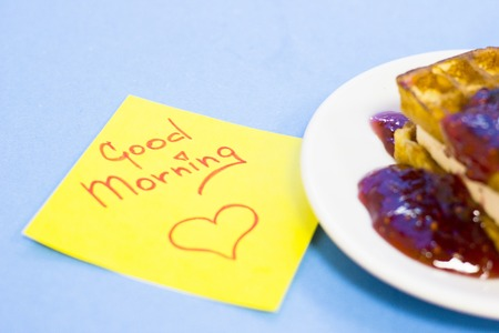 Delicious breakfast: a plate of fresh waffles with raspberry jam and Good Morning yellow sticker note on a blue background with copy space