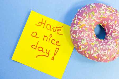 A pink glazed donut and have a nice day yellow sticker note on a blue background