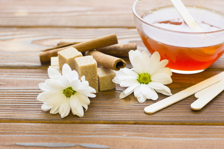 Set of sugaring essentials with natural honey, lemon, cinnamon and brown sugar on a natural dark wooden background