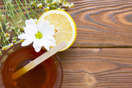 Dark natural wooden background with sugaring essentials: natural honey, medical camomile and lemon Stock Photo