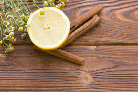 Dark natural wooden background with spa essentials: cinnamon sticks, lemon and medical camomile