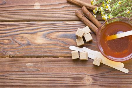 Dark natural wooden background with spa essentials: honey, cinnamon sticks, camomile and brown sugar cubes