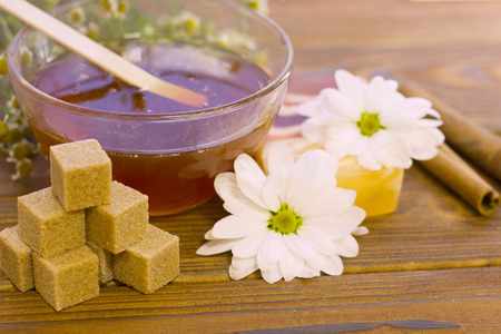 Set of sugaring essentials a bowl of honey, lemon, cinnamon and brown sugar on a natural dark wooden background Stock Photo