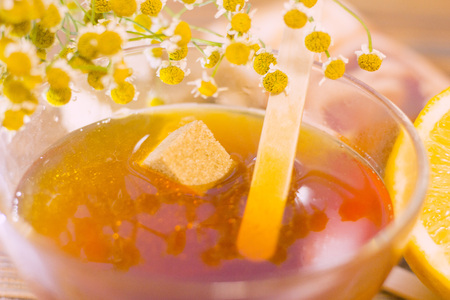 Spa procedures concept. Brown sugar cubes in a bowl of honey and camomile, natural dark wooden background, close up