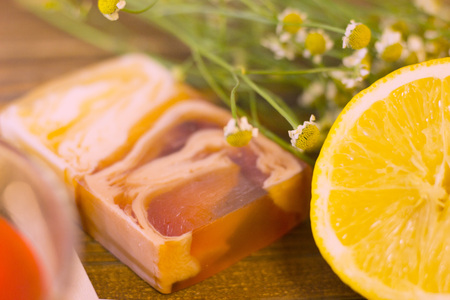A set of spa essentials with fruit soap, honey, lemon and camomile on a natural dark wooden background, close up Stock Photo