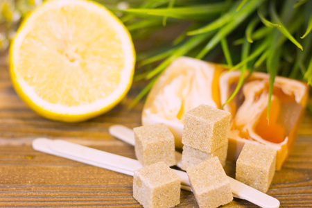A set of spa essentials with fruit soap, lemon, brown sugar and a green plant on a natural dark wooden background