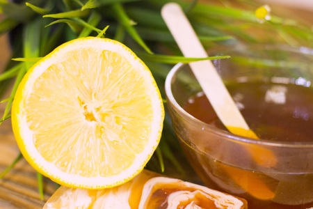A set of spa essentials with a bowl of honey, lemon, soap and a green plant on a natural dark wooden background, close up Stock Photo