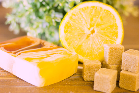 A set of spa essentials with fruit soap, lemon, brown sugar and a green plant on a natural dark wooden background, close up