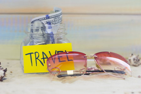 Planning for vacation, saving money for next trip. Sunglasses on sand background