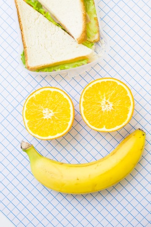 A happy face made of orange slices and banana and sandwich with lettuce, top view, white squared paper background with copy space