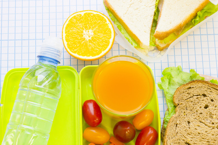 A green plastic lunch box with cherry tomatoes, carrot, a glass of juice,a bottle of water, sandwiches and fresh orange top view, white squared paper background with copy space