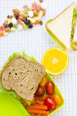 A green plastic lunch box with cherry tomatoes, carrot, orange, sandwiches and a buch of candied fruit, top view, white squared paper background with copy space Stock Photo