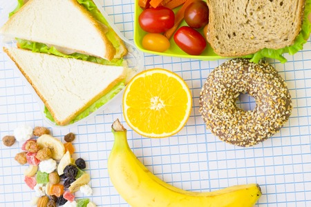 Lunch items set with vegetables in green lunch box, fresh fruit, candy fruit, sandwiches and chocolate donut,top view, white squared paper background