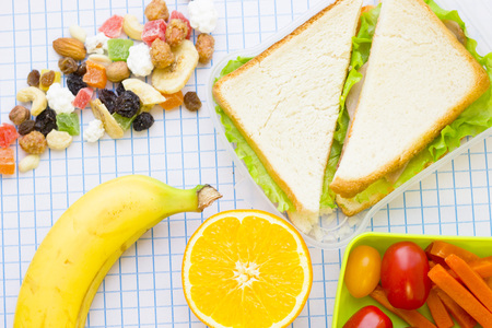 Lunch items set with vegetables in green lunch box, fresh fruit, candy fruit and sandwich ,top view, white squared paper background