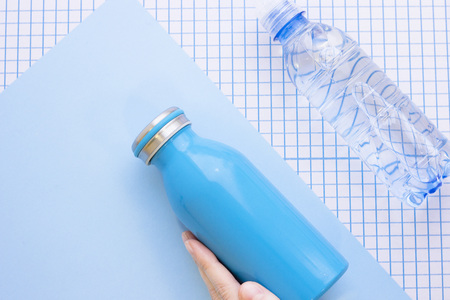 A bottle of water and a womas hand holding a blue bottle, top view, close up, blue and white squared paper background Stock Photo