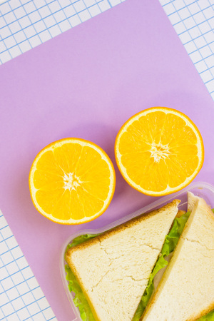Orange cut in half and a fresh sandwich in a box , top view, lilac and white squared paper background Stock Photo