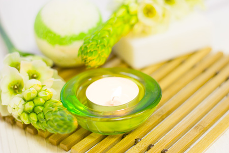 Spa and Floral concept, a spur of white flowers, a fragrant bath bomb, fruit soap and a burning candle in a green glass holder on a wooden mat, white wooden background, close up