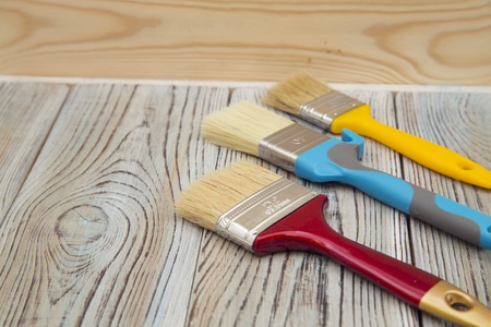 A set of wooden and plastic paint brushes on a grey wooden table against a light wooden wall, close up 版權商用圖片