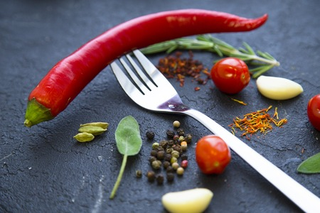 Pinches of dry spices, cherry tomatoes, beans, red chilli pepper and a fork on a black stone background with copy space, top view, flat lay