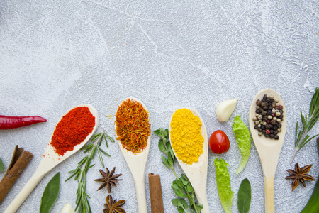 Dry spices and herbs in wooden spoons with fresh herb springs, cherry tomatoes, cinnamon and garlic on a light stone background with copy space, top view, flat lay