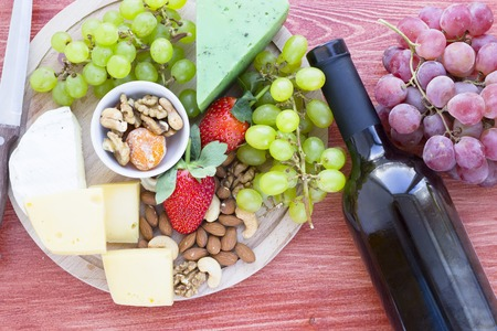 Snacks with wine - Strawberry, various types of cheeses, figs, nuts, honey, grapes on a red wooden background. Top view Stock Photo