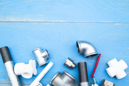 Various plumbers tools and plumbing materials including stainless steel pipe, elbow joint, wrench and spanner. Blue wooden background. Top view, copyspace