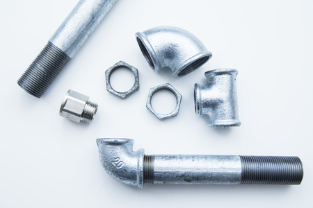 Various plumbers tools and plumbing materials including stainless steel pipe, elbow joint, wrench and spanner. White background. Top view, copyspace Stock Photo