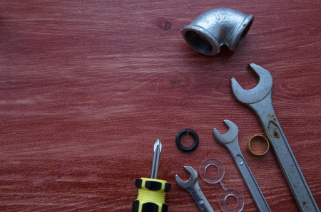 Various plumbers tools and plumbing materials including stainless steel pipe, elbow joint, wrench and spanner. Old red wooden background. Top view, copyspace Stock Photo
